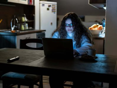 Teenage girl sitting in the dark using the computer