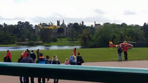 Bystanders watch as two emergency services helicopters land to treat injured passengers. (Facebook)
