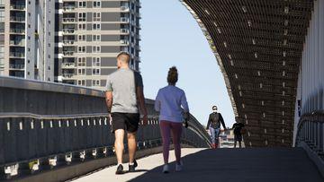 Residents walk over a bridge in Brisbane.