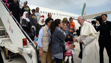 Pope Francis greets a group of Syrian refugees upon landing at Rome's Ciampino airport. (AAP)