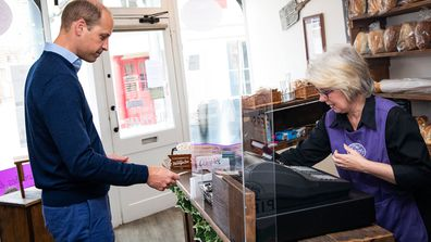 Prince William, Duke of Cambridge uses contactless payment to pay owner Teresa Brandon for his purchases during a visit to Smiths the Bakers, in the High Street on June 19, 2020 in King's Lynn, Norfolk.