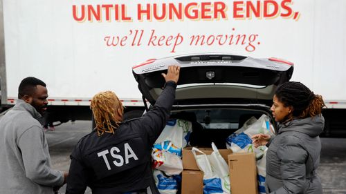 Federal workers who have missed their pay checks stock up on essentials at a food bank in Maryland.