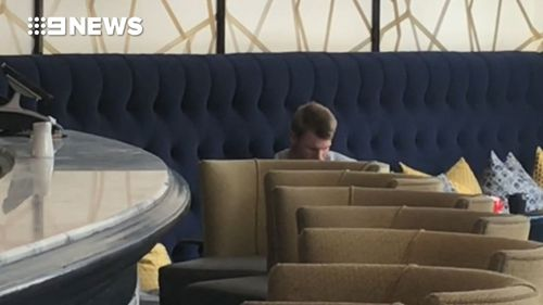 David Warner cuts a silent and lonely figure in the lobby of the Cullinan Hotel in Cape Town just days after the ball tampering bombshell hit the Australian cricket team. (9NEWS)