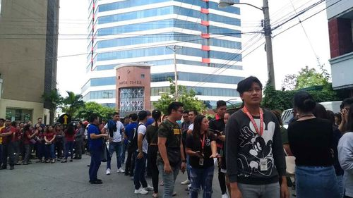 Office employees gather outside of buildings after a powerful earthquake was felt in Davao City, Philippines.