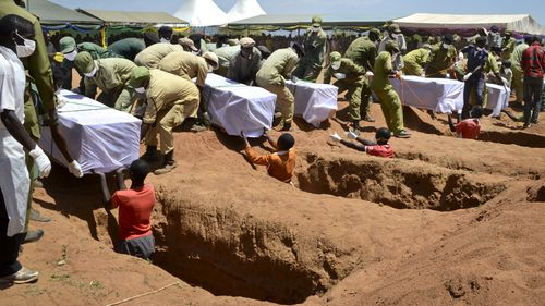 Coffins of some of the victims of the MV Nyerere passenger ferry capsizing are laid into graves during a mass burial ceremony on Ukara Island, Tanzania. (AAP)