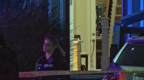 A police officer at the family home in Renton, Washington. (CNN)