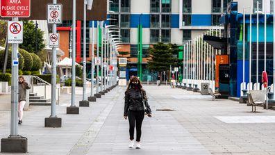 A lone pedestrian walks along a street in the Docklands precinct on September 25, 2020 in Melbourne, Australia.