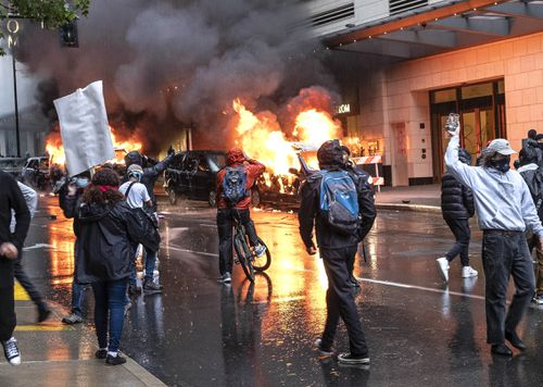 People set fire to vehicles during a protest in Seattle.