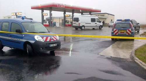 Police close off a service station in northern France where the fugitive gunmen were reportedly spotted.