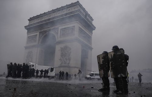French riot police clear the area around the Arc de Triomphe during violent clashes with Yellow Vest protesters in Paris.