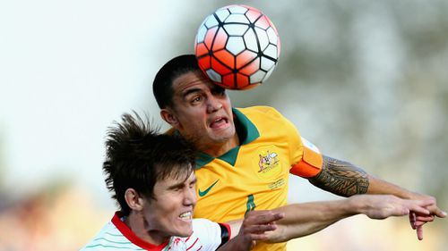 Tim Cahill competes for the ball with Eraj Rajabov of Tajikistan.