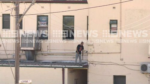 He was brandishing a machete but surrendered to police this morning (9NEWS)