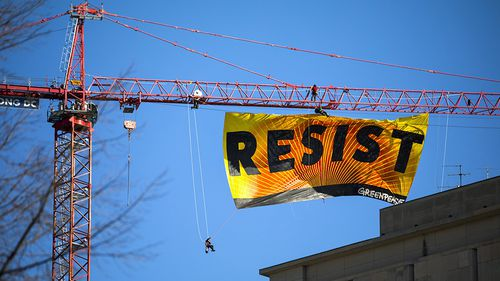 Greenpeace activists have hung a huge banner from a crane as an anti-Trump protest. (AAP)