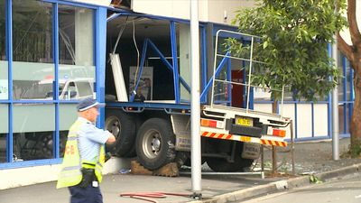 Truck crosses busy road and smashes into building