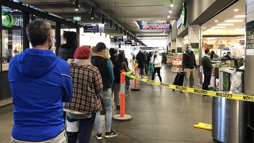 A long queue forms outside Woolworths supermarket in South Melbourne