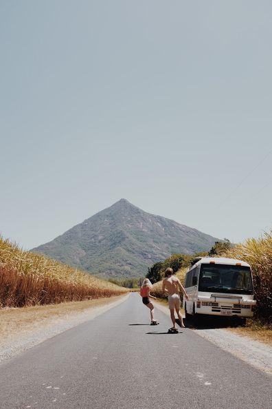Van life influencers skateboarding on a deserted road