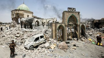 Members of the Iraqi Counter-Terrorism Service (CTS) gather outside the destroyed gate of the Al-Nuri Mosque in Mosul, July 2. Photo: AFP