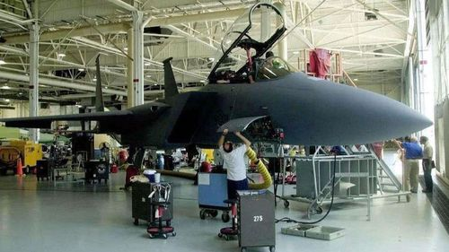 Workers at Boeing add the finishing touches to the final F-15E off the assembly line at the company's St. Louis facility on May 16, 2000.