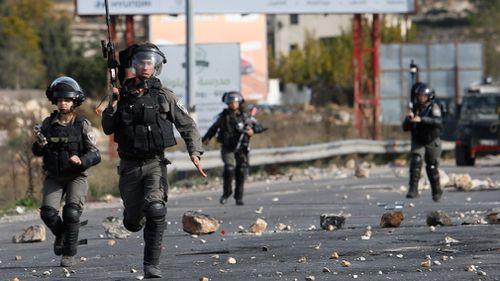 Israeli troops run during clashes with Palestinians. (AAP)