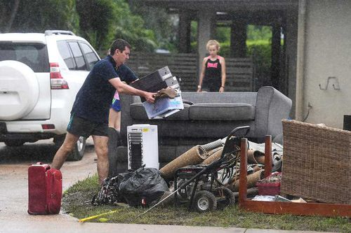 Residents dump furniture ruined by flood waters.