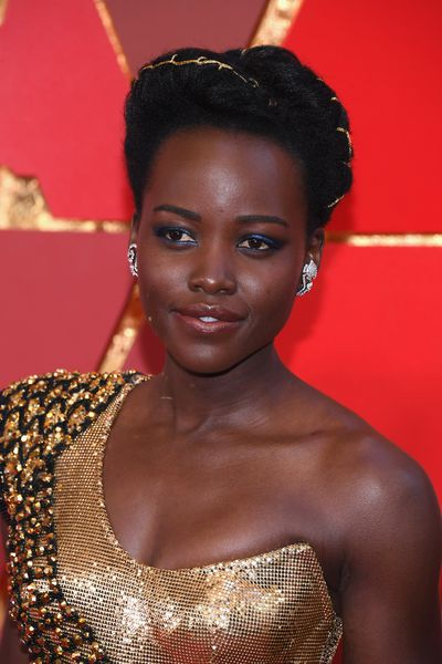 LupitaNyong'o is pure gold. The actress' upswept braided hair, peach lips and blue lids made her a stand-out.