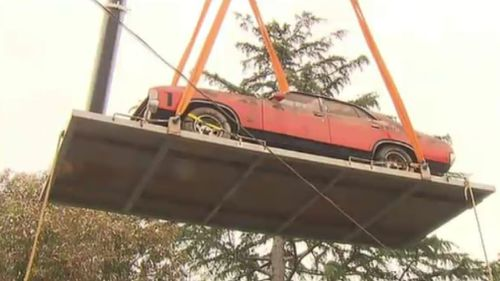 A 90-tonne crane was used to pluck the Ford from the backyard shed. (9NEWS)