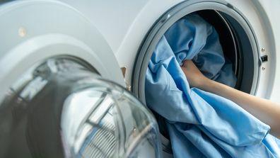 Person putting washing into a washing machine