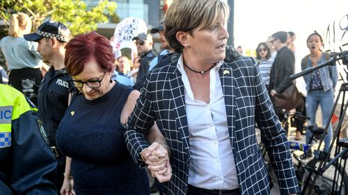 Christine Forster, Liberal councillor in the City of Sydney and sister of former prime minister Tony Abbott, is caught up in a crowd of protesters outside a fundraising event in Redfern, Sydney. (AAP)