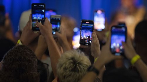 People record on their phones as Kanye West makes his first presidential campaign appearance on July 19, 2020.
