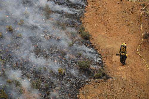 On the edge of destruction, a firefighter surveys damage close up. Picture: EPA