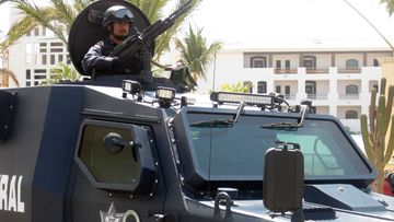 A heavily armed policeman keeps watch in Los Cabos, Mexico. (AAP)