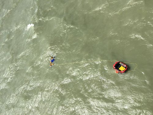 Three men were winched to safety 30km off the coast of Darwin when their boat sank.