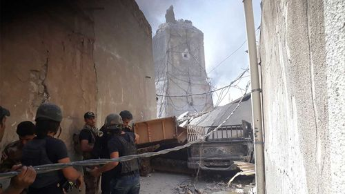 The Iraqi Army handles a massive cable outside the ruins of the destroyed leaning minaret of al-Nuri mosque. (Owen Holdaway)