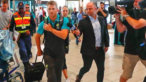 David Warner faces a media pack as he arrives in Johannesburg. (EPA/AAP)