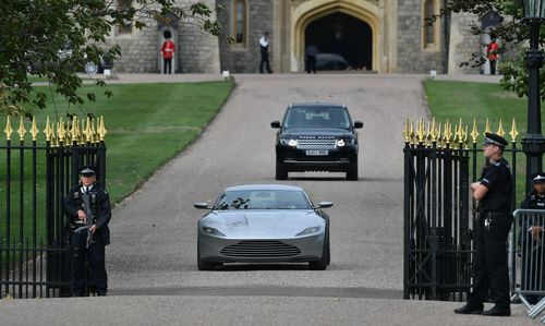 The happy couple head off toward married life through the Windsor Castle gates in the Aston Martin.
