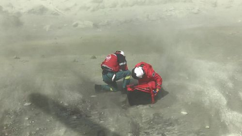 Two of the first responders kneeling among the moon-like dust of White Island following the deadly eruption.