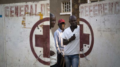 Employees guard the door of the Katuba Reference Hospital in Lubumbashi, Democratic Republic of the Congo.