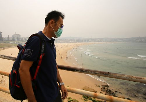 A tourist looks over a smoky Bondi Beach, in Sydney's eastern suburbs. Thick smoke descended on the city yesterday reducing visibility levels and sending air quality safety levels plummeting.