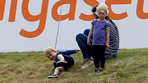 Prince George rolls about on the grass. (Steve Parsons/PA Wire)
