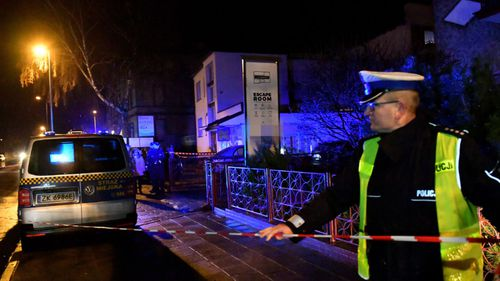 Police at the scene of the fire tragedy in northern Poland.