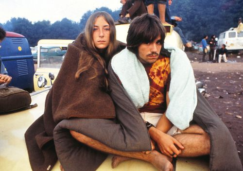 A young couple, sitting on a van, at the Woodstock Music Festival, New York
