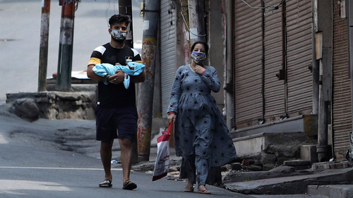 Indians wearing face masks as a precaution against the coronavirus walk past closed market during reimposed weekends lockdown to prevent the spread of new coronavirus in Jammu, India, Sunday, July.26, 2020.(AP Photo/Channi Anand)