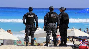 Police stand guard on the beach in Cancun.