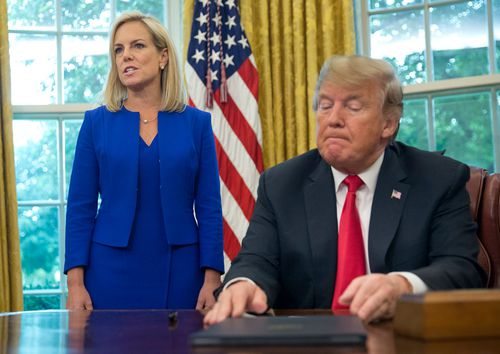 Trump listens as Homeland Security Secretary Kirstjen Nielsen addresses members of the media before Mr Trump signs an executive order to end family separations at the border.