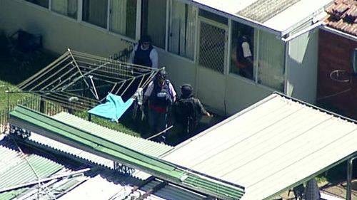 Police search the backyard of a property in Guildford. (9NEWS)