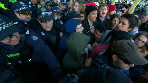 Police and protesters crush together outside the Melbourne event venue.