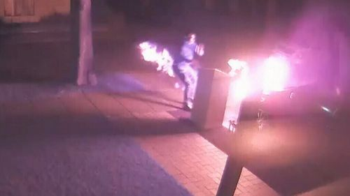 He then throws it onto a car near the Newington home as the item erupts into a second fireball. (Supplied)