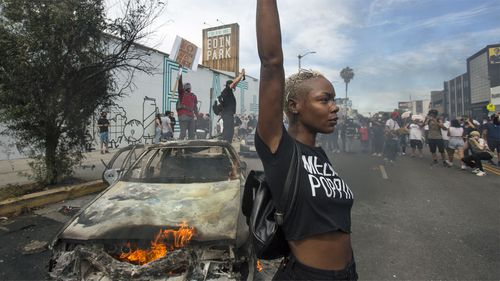 A protester poses for photos next to a burning police vehicle in Los Angeles.