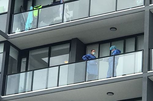 Police examine the balcony where the woman plunged from. (9NEWS)