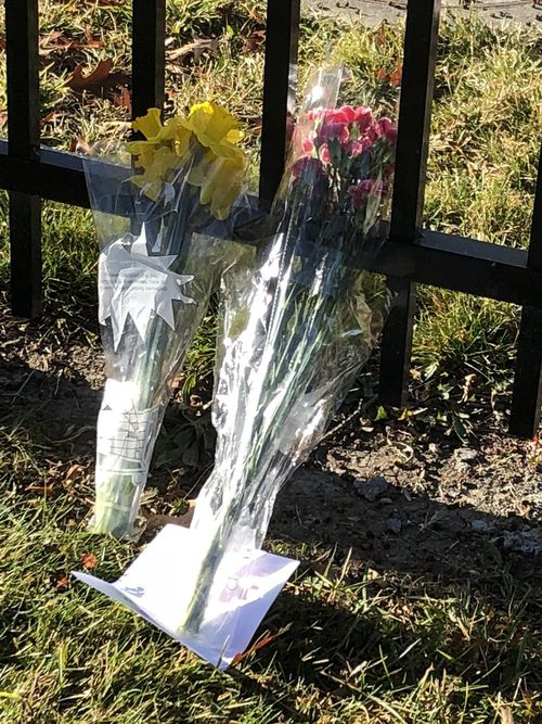 Flower tributes are left on the school fence. Picture: 9NEWS